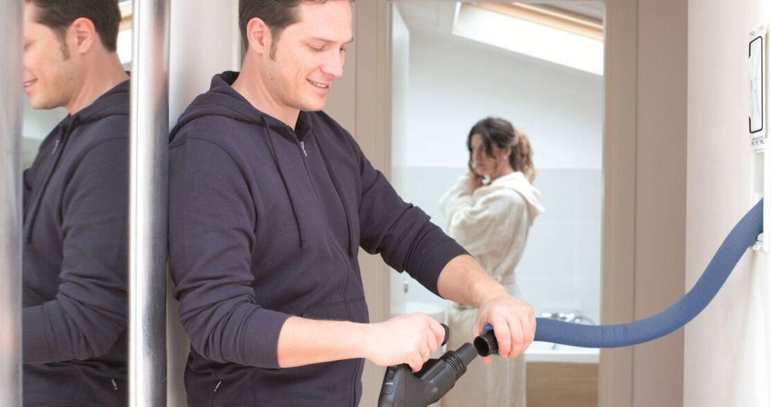 Mann benutzt einen Zentralstaubsauger